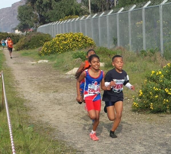 Junior striders from the Southern Striders Athletic Club running on a country path