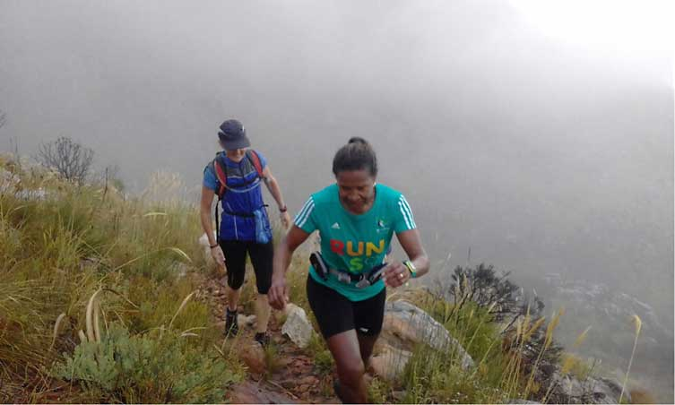 Trail runners on a path on a misty mountain